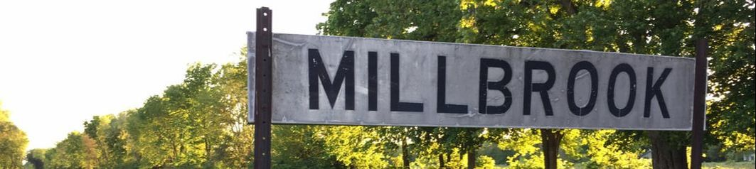 Millbrook Sign Next to Train Tracks